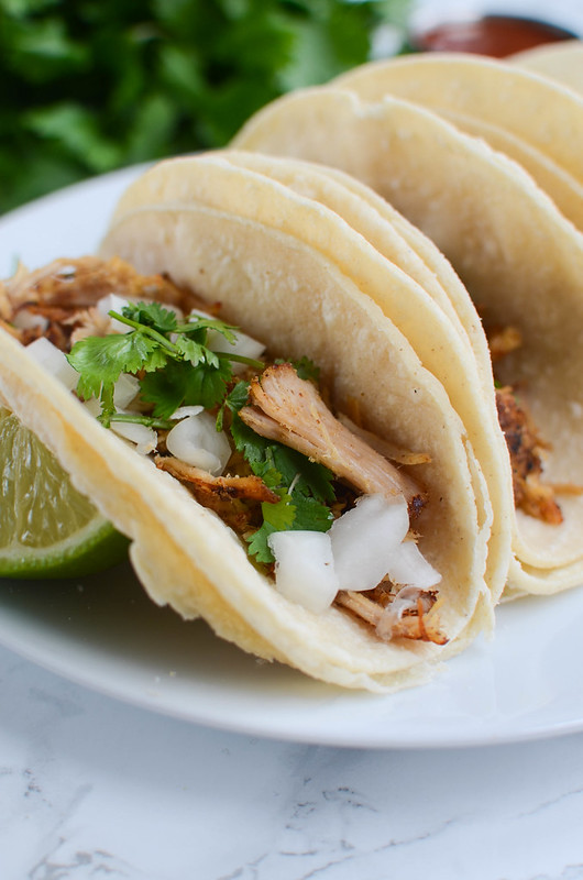 Slow Cooker Carnitas Street Tacos - delicious tender pork on top of corn tortillas with diced onion, fresh cilantro, and salsa on top! Your whole family will love this easy dinner!