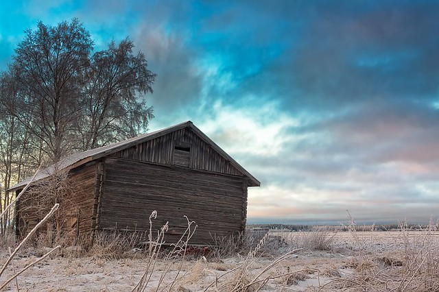 Winter Sunset Behind An Old Barn House