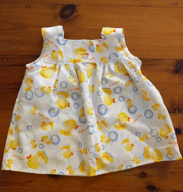 An image of a baby dress in a white fabric with yellow rubber duck and bubble print.