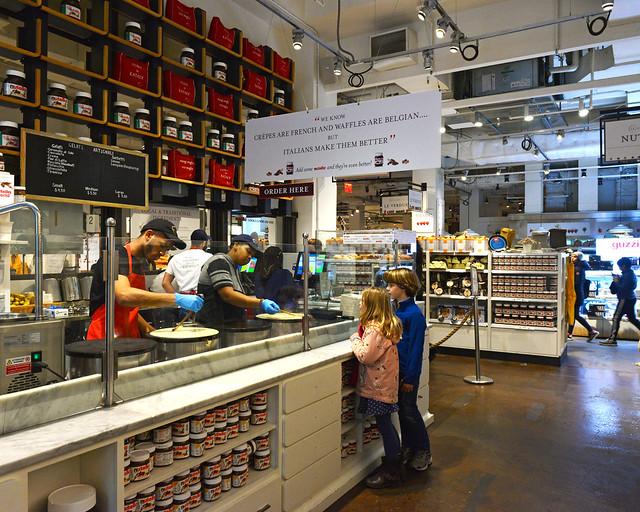 Interior del Nutella Bar de Nueva York mientras se hacen crepes y niños mirando