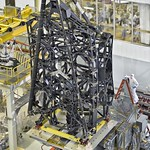 The telescope structure includes the primary mirror backplane assembly; the main backplane support fixture; and the deployable tower structure that lifts the telescope off of the spacecraft. The three arms at the top come together into a ring where the secondary mirror will reside. Image credit: NASA/Chris Gunn
