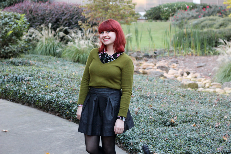 Olive Green V-neck Sweater over a Floral Top and Pleated Leather Skirt