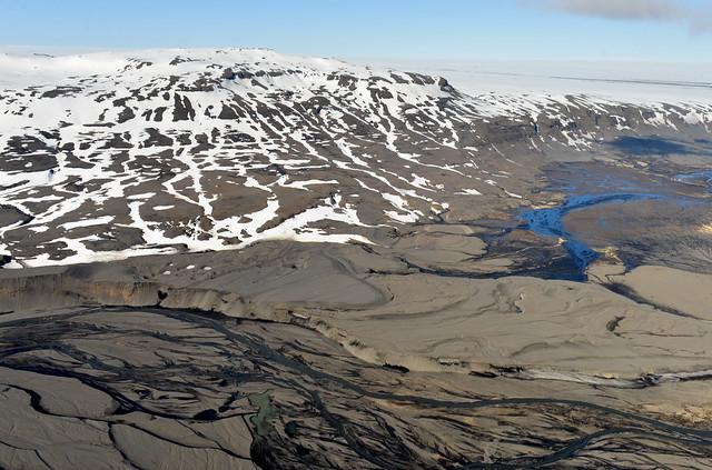 Rios de agua sobre ceniza al borde de un glaciar en Islandia