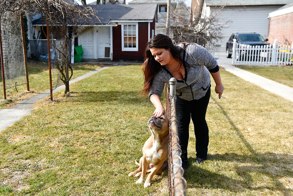 © 2016 by The York Daily Record/Sunday News. Christina Whelan, 27, of New Jersey, pets a neighbor dog named Killer while taking a cigarette break outside the Pennsylvania Avenue house where she lives and which is operated by Choices Recovery House, on Monday, March 7, 2016. Whelan, whose addictions are heroin and Xanax, said she had been to 16 different rehabilitation or treatment centers in states including New York, Florida, California and Tennessee.