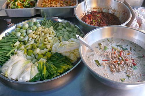 במגש הירקות: שעועית ירוקה, כרוב סיני חלוט וטרי, במבוק, מלפפונים, חצילונים, קאנה חלוט, ירק מבושל ממשפחת הדלועים
