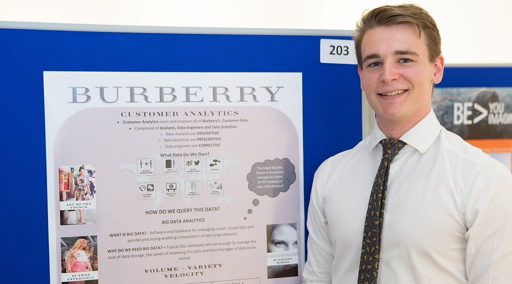 Photo of Christian Woolf with his poster about his placement at Burberry