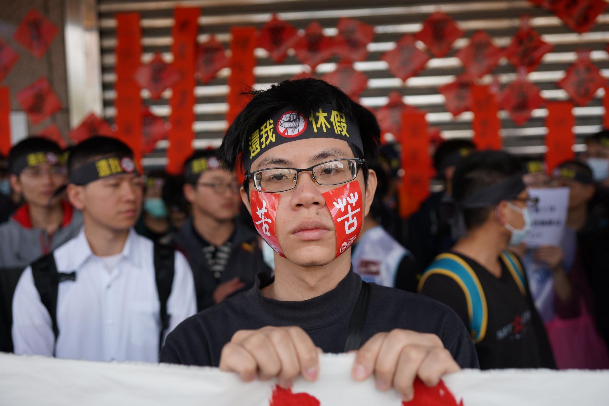 """台铁员工在脸上张贴""""苦""""字。(摄影:王颢中)"""