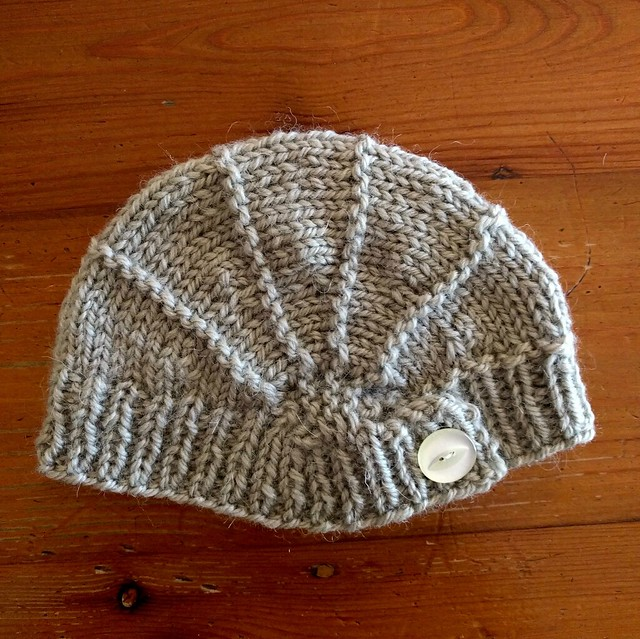 A handknitted green baby hat.