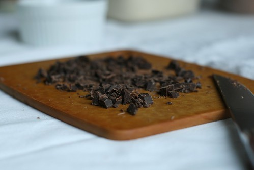 A bunch of chocolate chunks on a cutting board with a recently used knife to cut it.