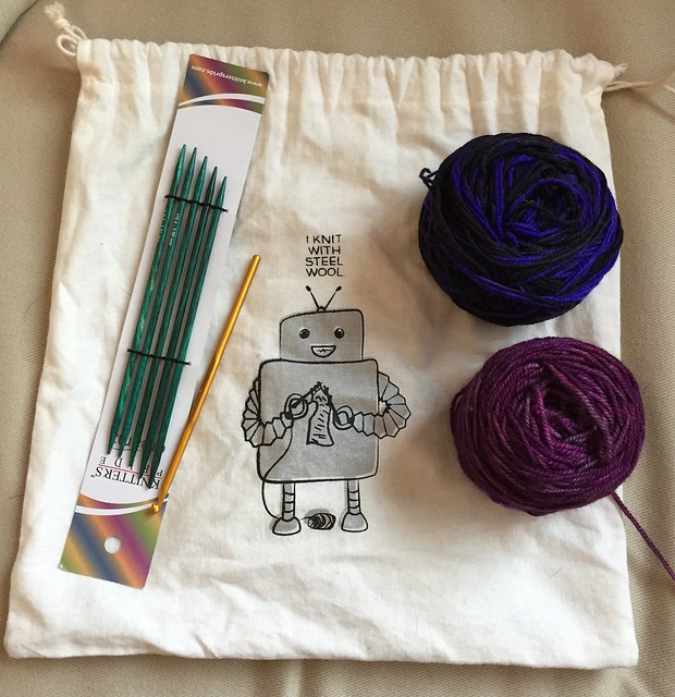 A knitting project containing 2 yarn balls, some needles, and a knitting bag that has a robot on it. The robot, adorably, is saying,