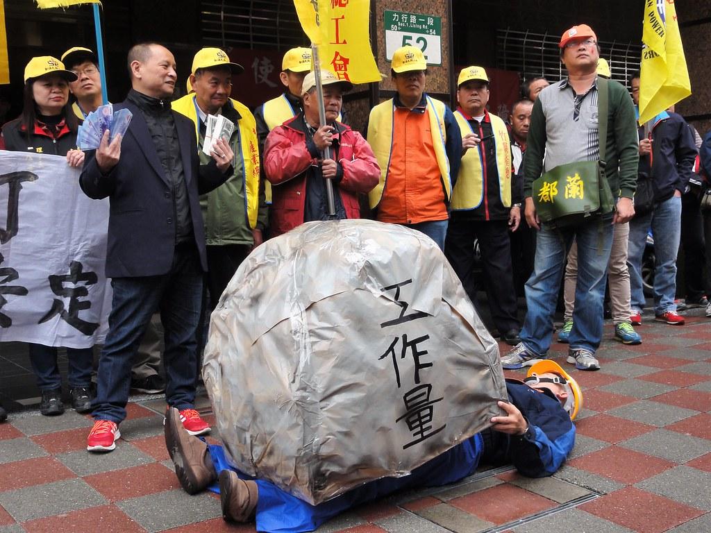 工會演出行動劇,表現出工人被休假挪移後加重的工作量壓垮。(攝影:張智琦)