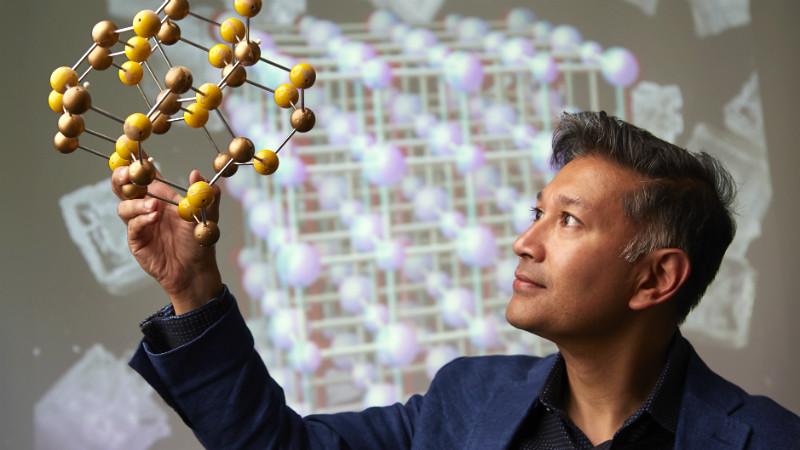 Professor Saiful Islam holds a scientific model.
