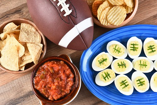 Super Bowl foods and a football on a wooden table
