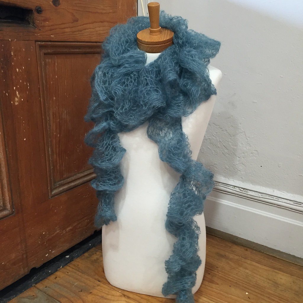 a scarf knitted in rowan kidsilk creation in teal, displayed on a white bust