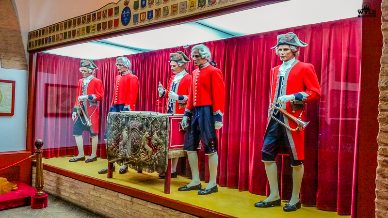 Uniforms from the Spanish military that are displayed in the Seville Bullring Museum. They are red with black shorts and long white socks.