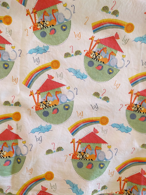 An image of fabric from a blanket. Pattern is Noah's Ark filled with animals, rainbows and pairs of animals on white backing.