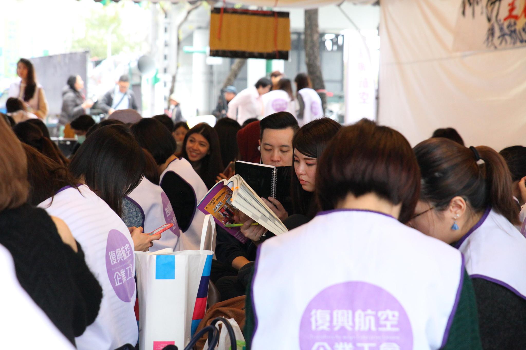 夜宿現場,失業員工手持國考教科書,為自己尋覓一個相對「穩定」的未來。(攝影:陳逸婷)