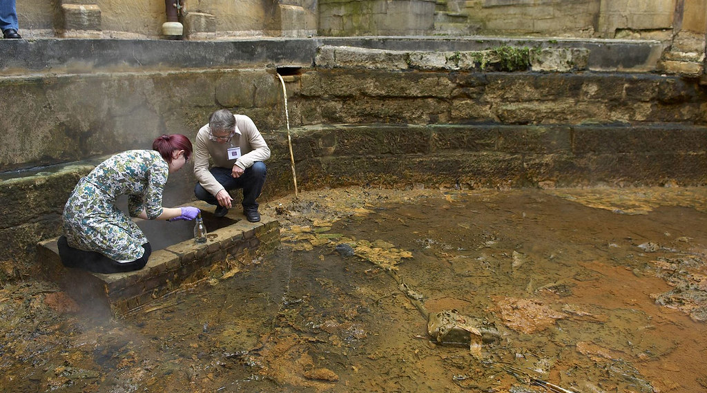Two researchers collect algae from the floor of the Roman Baths in Bath