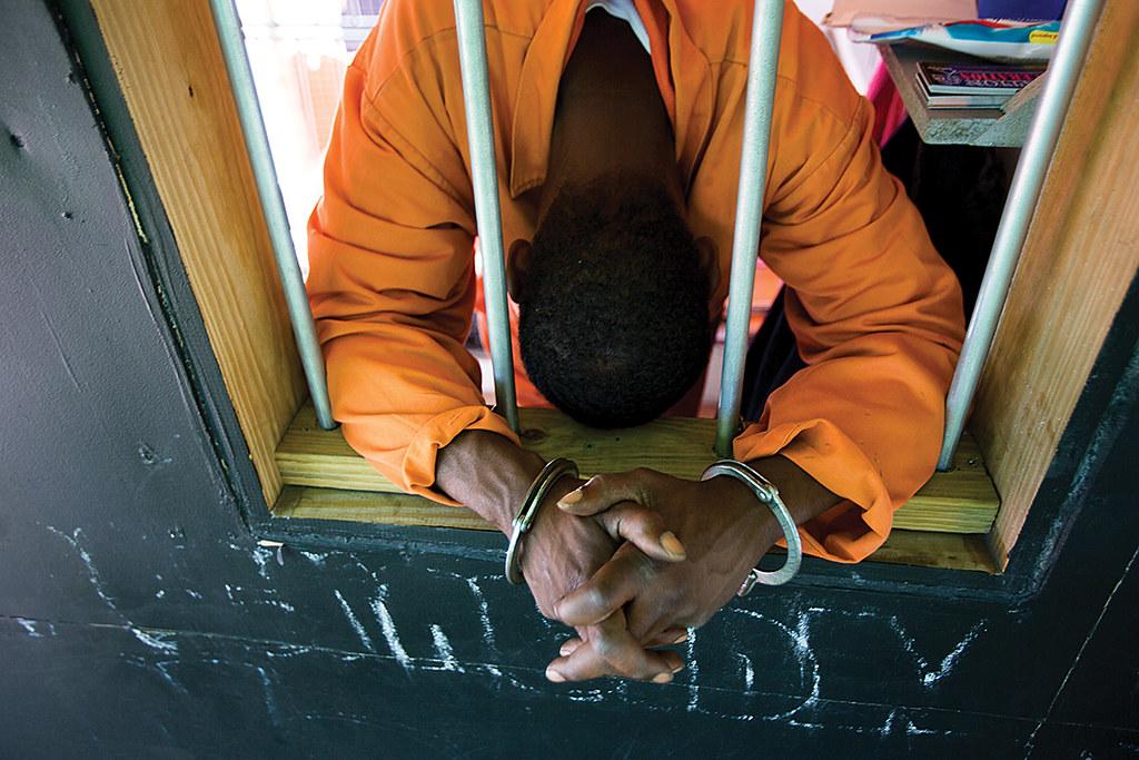 A black man behind prison bars