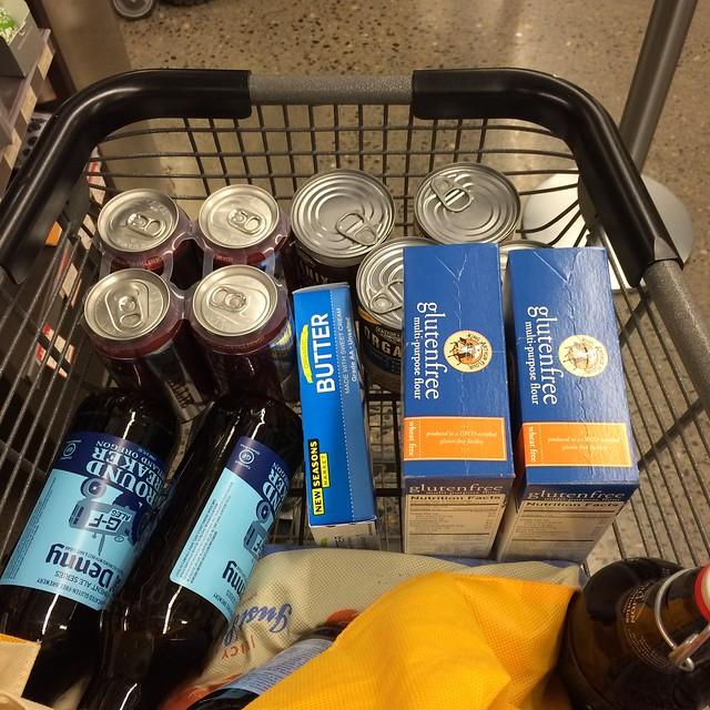 A small shopping carte filled with groceries: beer, butter, dog food, gluten-free flour mix, and kombucha.