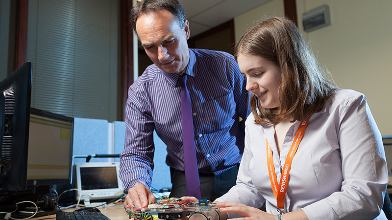 female student and male employer at a desk looking at a circuit board