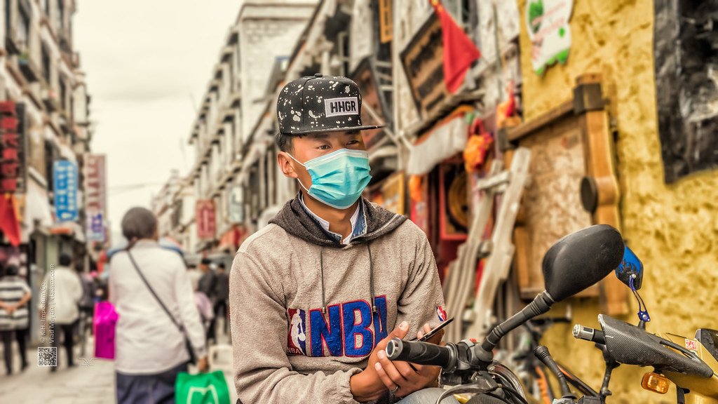 Tibet, candid shot of a youngster wearing a surgical mask sitting on the scooter in the streets of Lhasa (China), 06-2016, 92 (Vlad Meytin, vladsm.com)