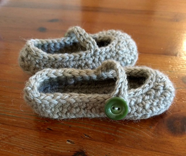 Handknitted green baby booties.
