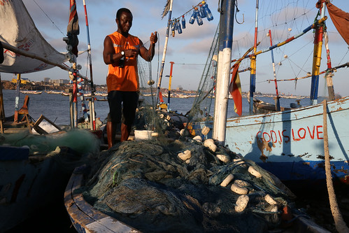 A fisherman prepares his fishing nets in Jamestown Fishing Village in Accra, Ghana | by World Bank Photo Collection