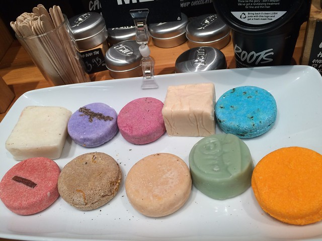 A platter full of colorful, circular cakes from LUSH cosmetics. Two are squares. Orange, pinks, blue, green, gold, beige.