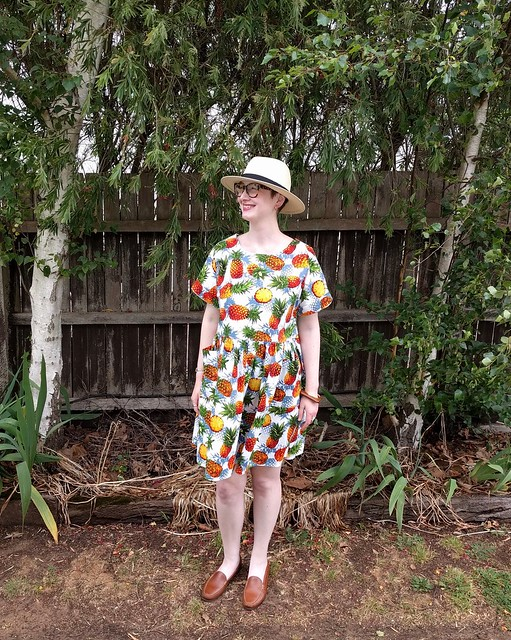 A woman stands in front of a garden fence, wearing a pineapple print dress and panama hat.