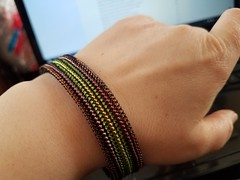 woven bead bracelet in reflected stripes of brown, eggplant, green and chartreuse