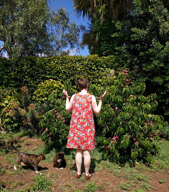 A woman stands in a garden. She wears a knee-length tent dress in an orange tropical floral print. A black and white cat sits next to her.