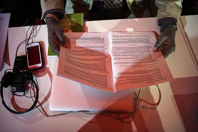 談判代表手拿會議文件閱讀。攝影:Benjamin Géminel。圖片來源:COP PARIS