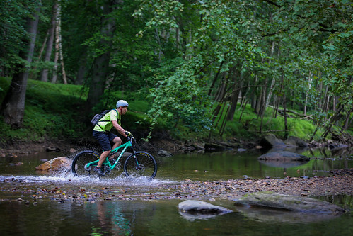 Photo of mountain biker crossing stream