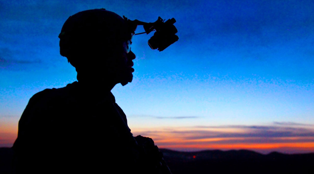 Silhouette of a soldier against a sunset. He's wearing a helmet and binoculars.