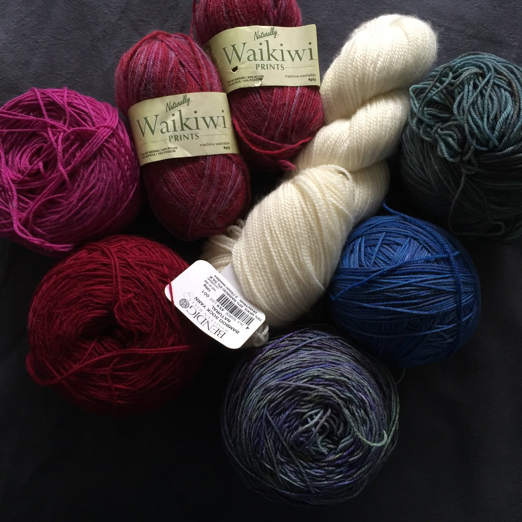 a collection of yarns to be knit into socks, in assorted colours and fibre compositions
