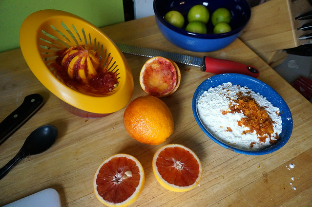 A juicer, covered in red pulp, sits near two orange shells and a bowl of powdered sugar covered in zest. The blood orange pulp really does look bloody.