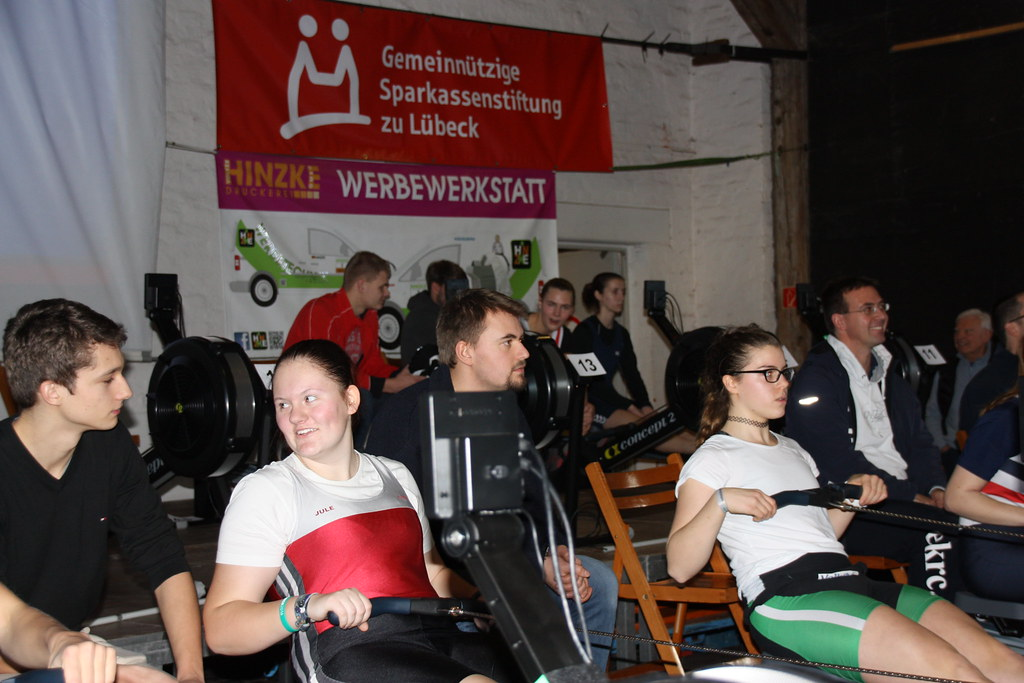 Sportlerinnen auf dem Ruder-Ergometer im Hintergrund betreut von ihren Trainern