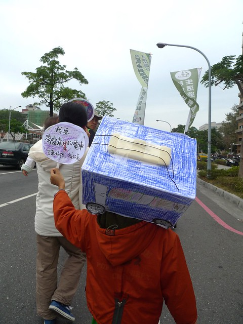 圖中為住在台南的小朋友自製低污染的電車,把電車戴在頭上,告訴大人,「我要零廢氣的電車」!