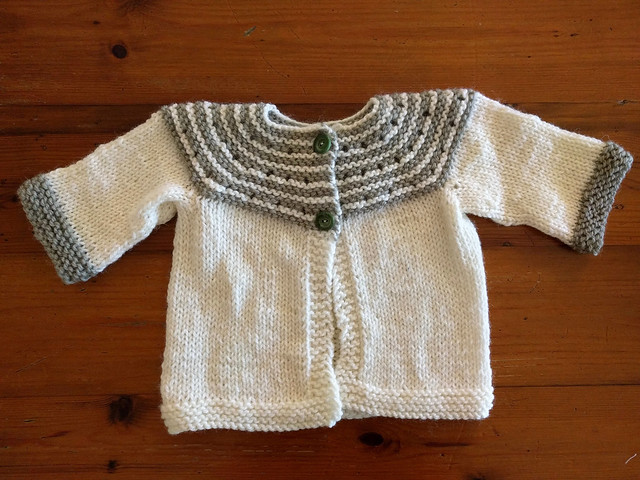 A handknitted green and white baby cardigan.