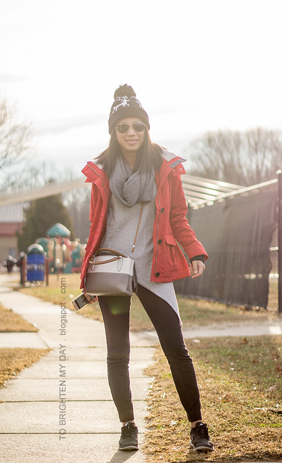 black reindeer knit cap with pom, red performance jacket, gray asymmetric top, colorblocked crossbody bag, herringbone and plaid infinity scarf, black skinny jeans, black sneakers