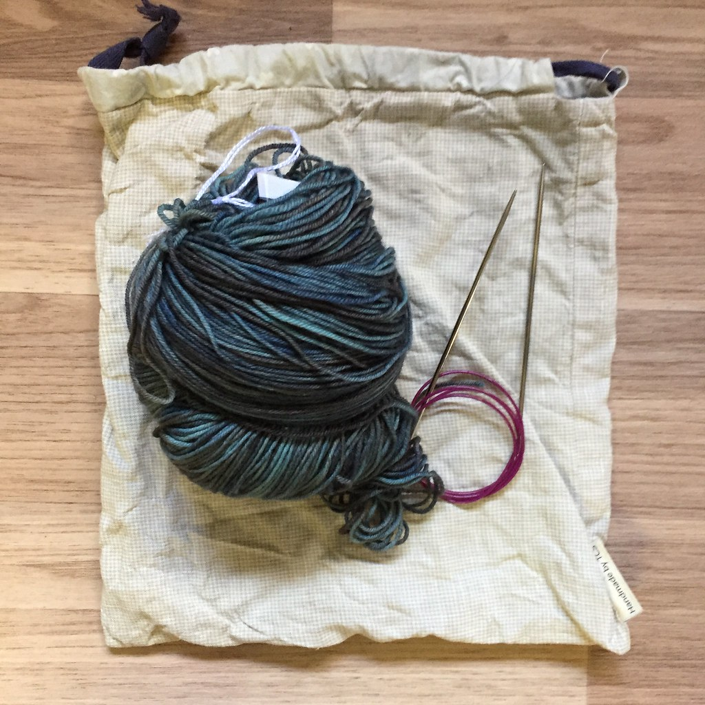 a cake of miss click clack 'the darkness of kelly's blues' on merri creek sock on a project bag, needles at the ready