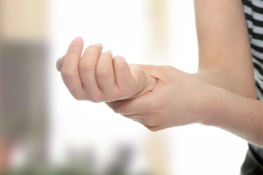photo of woman clutching her painful wrist
