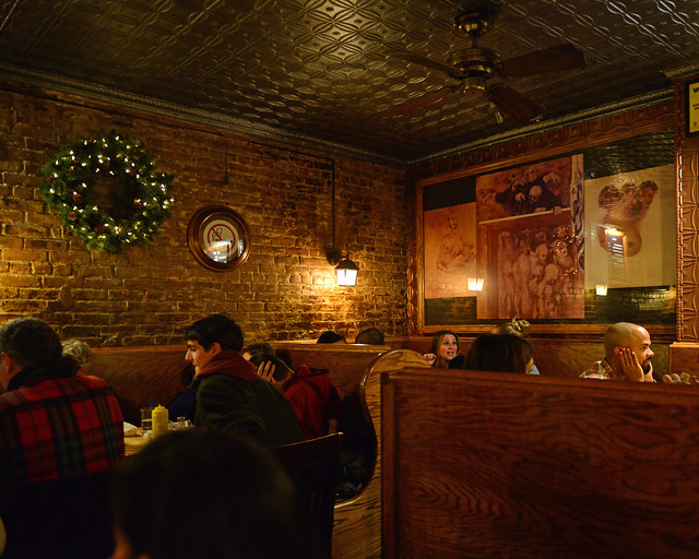 Interior del restaurante Corner Bistro de Nueva York con paredes de piedra, luz baja y decoración navideña