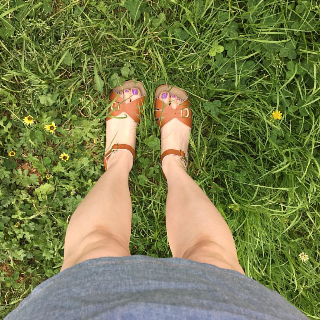 showing off my tan saltwater sandals on the grass