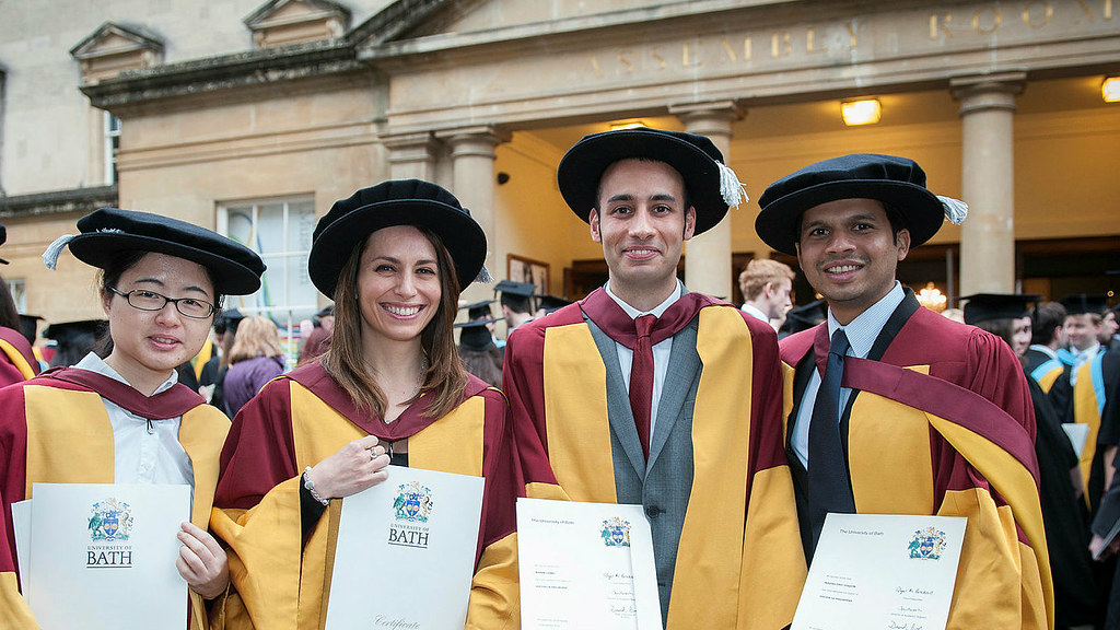Four happy MBA students graduating