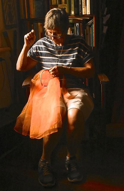 Jill Weaver hand stitching an orange veil in morning sunlight, February 2017