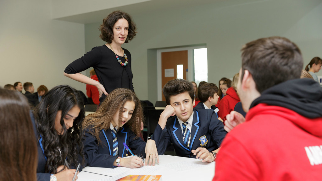 Agnes Mason and a Student Ambassador helping some Year 9 students at their table during the Taster Day
