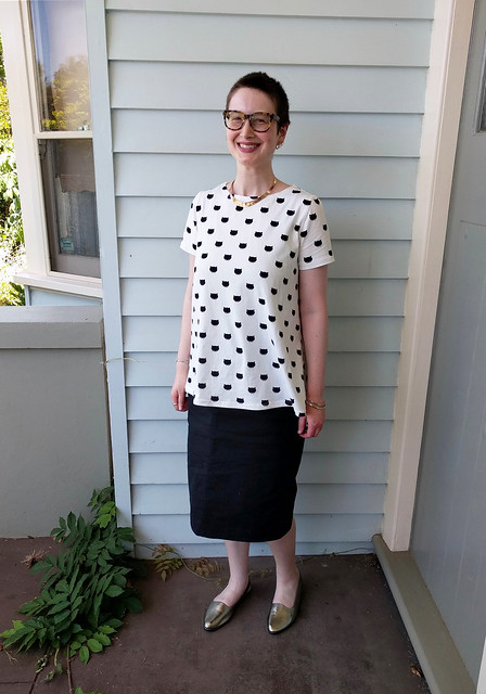 An image of a woman standing in a veranda. She wears a white tee with black cat print on it, and a straight black denim skirt, with gold necklace and shoes.
