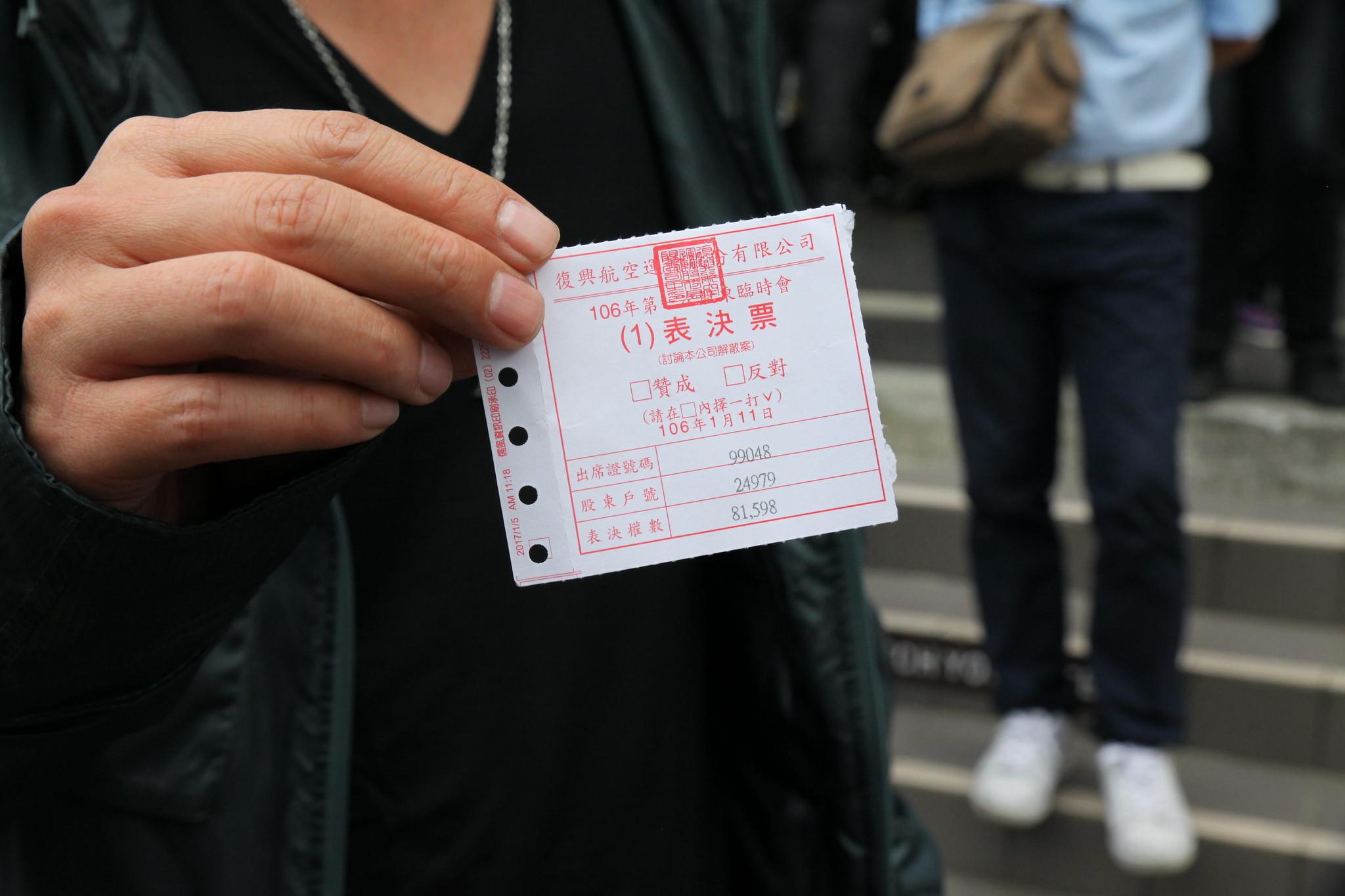 小股東手持第一案選票,表示根本沒有時間投票,會議就公布投票結果了。(攝影:陳逸婷)